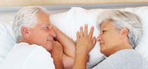 elderly couple laying next to eachother