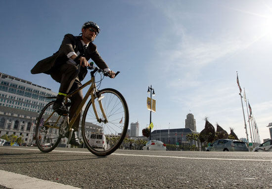 bicyclist wearing a suit and a helmet