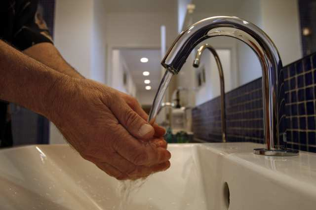 hands being washed under a sink's faucet