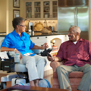 elderly couple in living room. Elderly woman is in an electric wheelchair