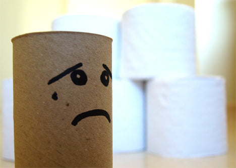 Toilet paper in the background with the cardboard cylinder in focus with a sad face drawn