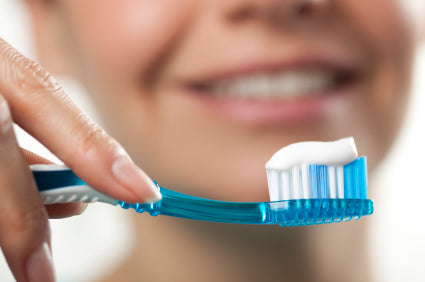 woman holding a tooth brush with toothpaste on the brush's bristles