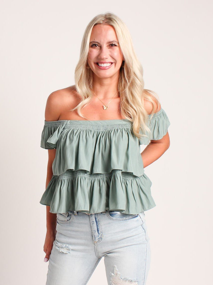 woman in a sage blue tiered blouse and distressed jeans