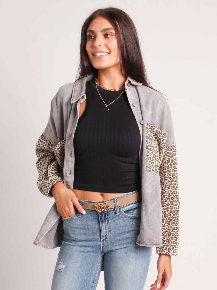 woman wearing a leopard print shacket, black top, and jeans
