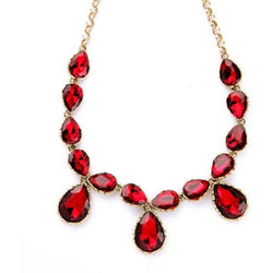 Closeup of red gems on Ruby Red Tear Drop Statement Necklace on white background.