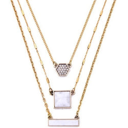 Three layers of gold plated necklaces; one with a rectangular white stone, one with a square white stone and the last with a hexagon with tiny crystals on a white background.