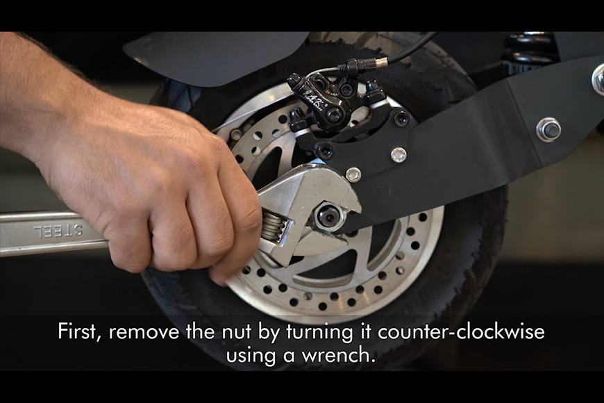 Remove the nut and washer on one side of the e-scooter tyre