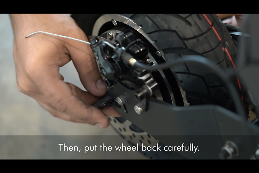 Put the wheel back carefully, insert the washers, and screw the nut back.