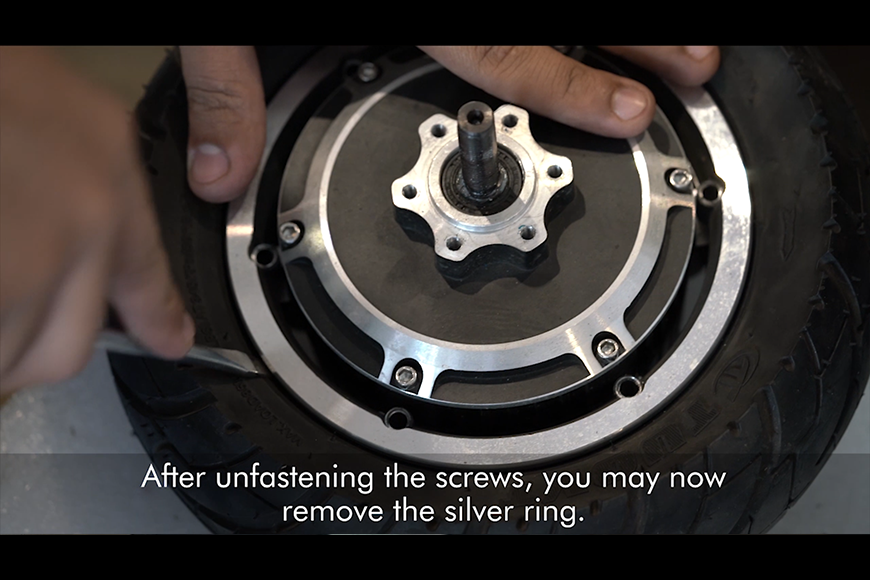 Take out the outer screws and the silver ring.