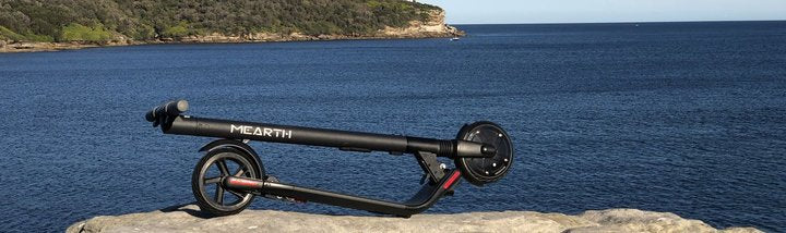 Image of a Mearth folding electric scooter against ocean background.