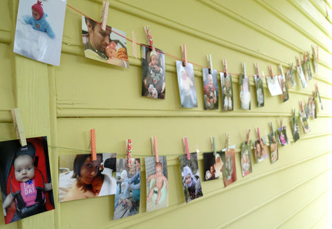 Washi tape decorated clothes pins on photo wall first birthday activity