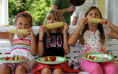 three girls eating corn on a porch swing at a summer party