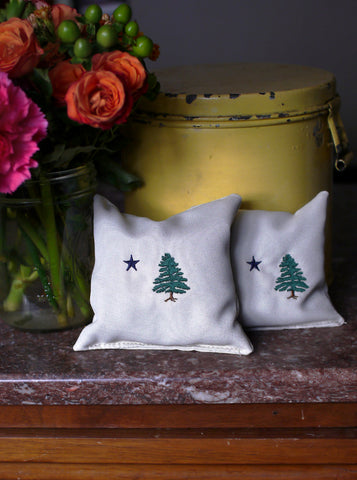 Two small balsam sachets made in Maine by 1901 Maine Flag are sitting on an antique cabinet with dark orange and green flowers next to a yellow antique canister