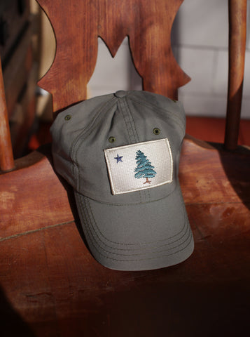 1901 Original Maine Flag insect-repelling baseball Cap in olive green sitting on a wooden chair in the sun.