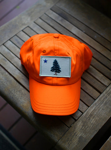 1901 Original Maine Flag insect-repelling baseball cap in hunter safe blaze orange sitting on a wooden bench in the sun.