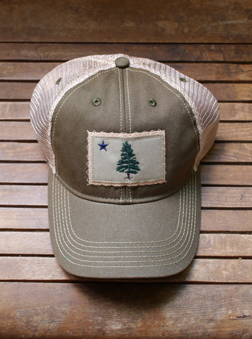 1901 Maine Flag trucker hat is artfully distressed for that lived-in look and feel. Olive trucker hat with tan back mesh and Maine flag appliqué on the front center