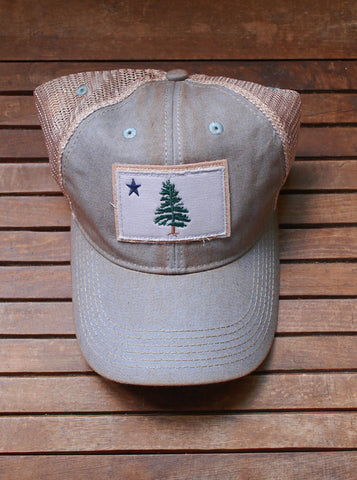 1901 Maine Flag trucker hat in a light grey/blue color-way is artfully distressed for that lived-in look. Cap displayed on antique wooden bench.