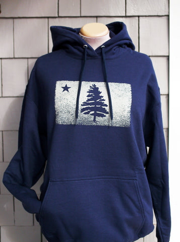 Navy blue hooded sweatshirt features our signature 1901 distressed Maine flag. Sweatshirt is displayed on a mannequin against grey cedar porch shingles..