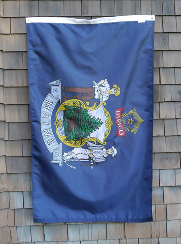 Maine State Flag with Official Coat of Arms. Royal Blue flag hanging against grey wood shingled barn.