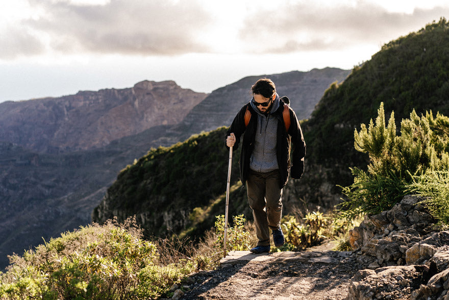 person mindfully hiking up a mountain