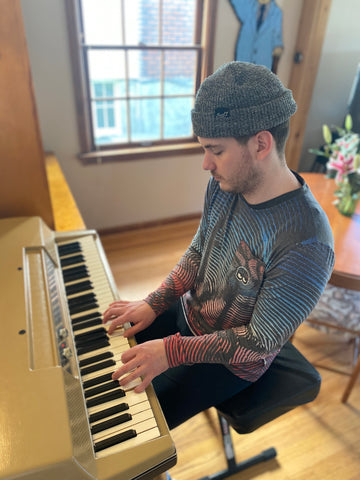 man playing piano wearing a long sleeve tee and beanie in a room with a window