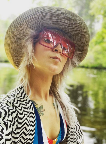 woman with sunglasses and hat posing for a selfie