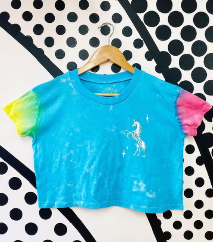 tye dye crop top hanging on a wooden hanger the top has a yellow sleeve, blue body and pink sleeve