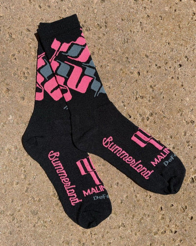 Pink, grey, and black pair of socks laying flat on concrete