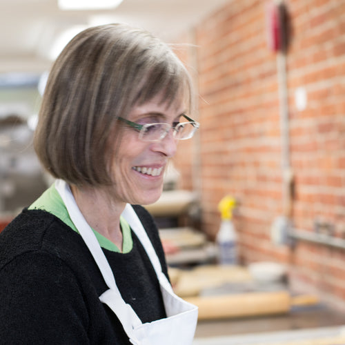 Woman with glasses and an apron looking down and smiling against brick background