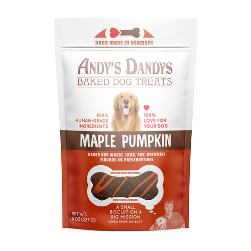 Front of white and orange pouch of tasty Andy's Dandys Maple Pumpkin flavor mini bone shaped baked dog biscuits drizzled with orange yogurt icing