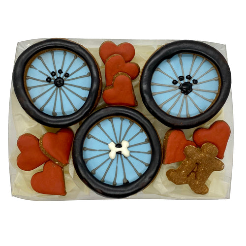 Three decorated bike wheel shaped Andy's Dandys baked dog treats with several small red heart dog treats and a person shape in a gift box