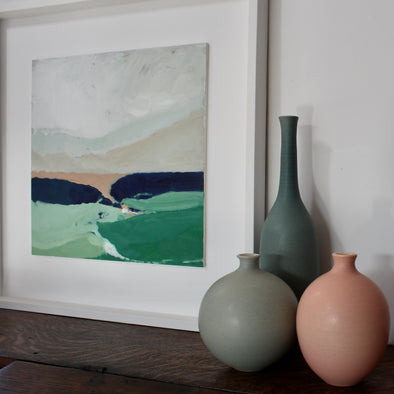Three ceramic bottles next to a framed abstract painting of the countryside