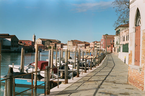 canal with boats and street in Venice