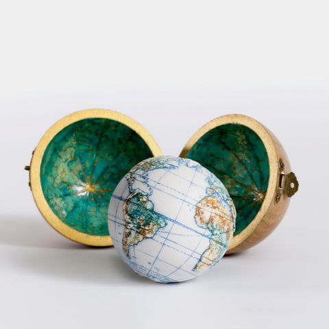 a miniature globe sitting outside a spherical wooden case