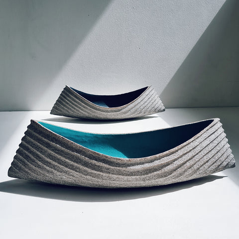 Two ceramic boat shaped dishes with ribbed outsides and blue interiors