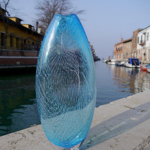 Blue glass vase photographed next to canal in Venice