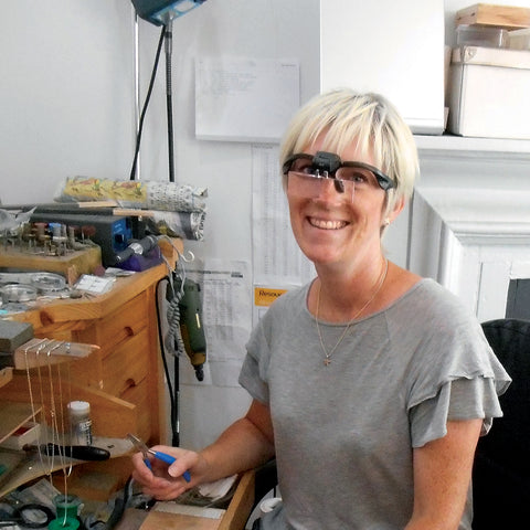 Woman sitting at jewellery work bench wearing specialist jeweller's goggles