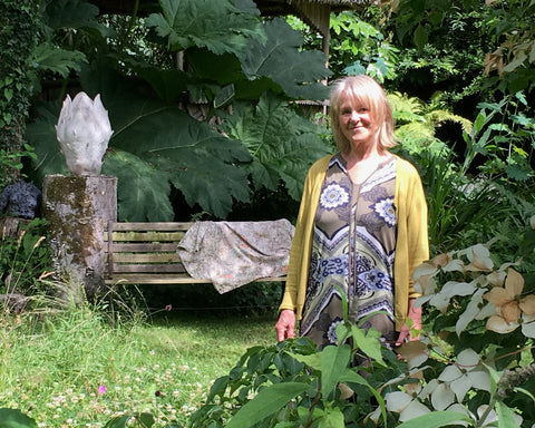 Ceramicist Pauline Lee wearing a yellow cardigan over a black dress standing in her garden next to a ceramic sculpture