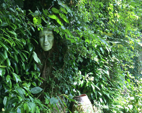 A ceramic face mask hanging among the green leaves of a bush