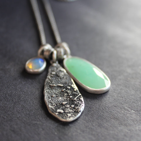 three part silver necklace with a large green stone and a small purple one