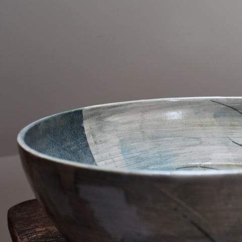 part of a large blue ceramic bowl on a wooden table