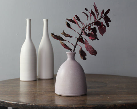 Ceramic bottles by Lucy Burley on a wooden table