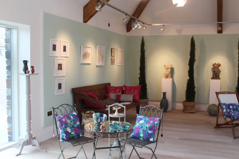 Gallery interior - art and sculpture in a room with pale green walls
