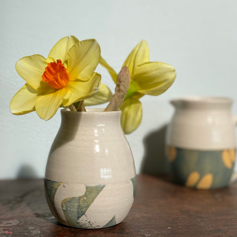daffodils in a small ceramic vase with a small ceramic jug in the background