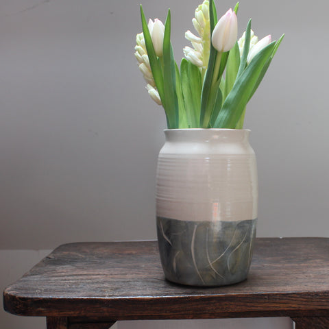 white tulips in a ceramic vase with a green glaze to the lower half sitting on a wooden table