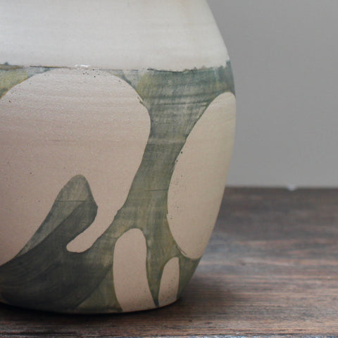 the lower half of a ceramic vase showing the green glaze detail