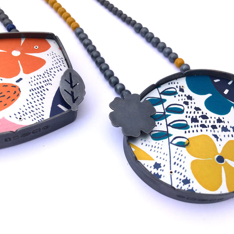 Brightly coloured enamel jewellery on a beaded chain