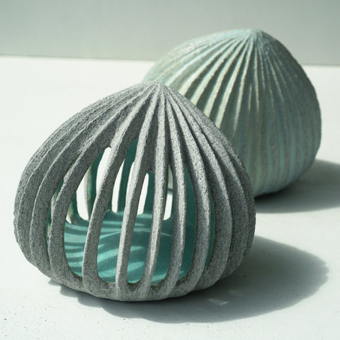 Hand carved ceramic pods with pale blue insides by ceramic artist Michele Bianco