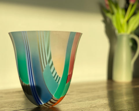 Ruth Shelley multicoloured glass vessel on a wooden table