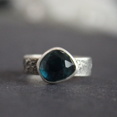 silver ring with a teal blue stone